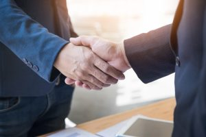 Two buisiness people shaking hands indicating they have made a deal