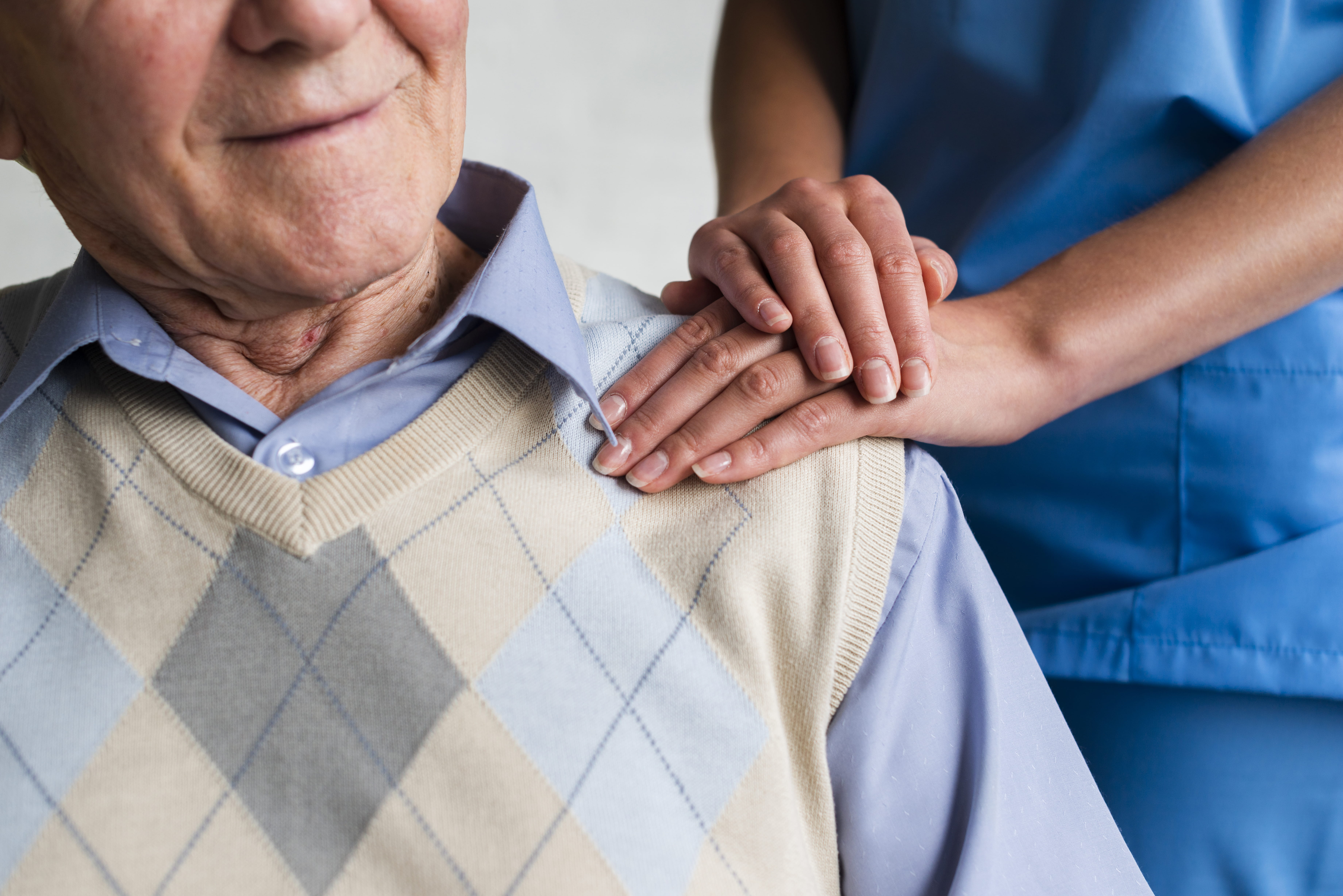 Carer placing supportive hand on the shoulder of an elderly man