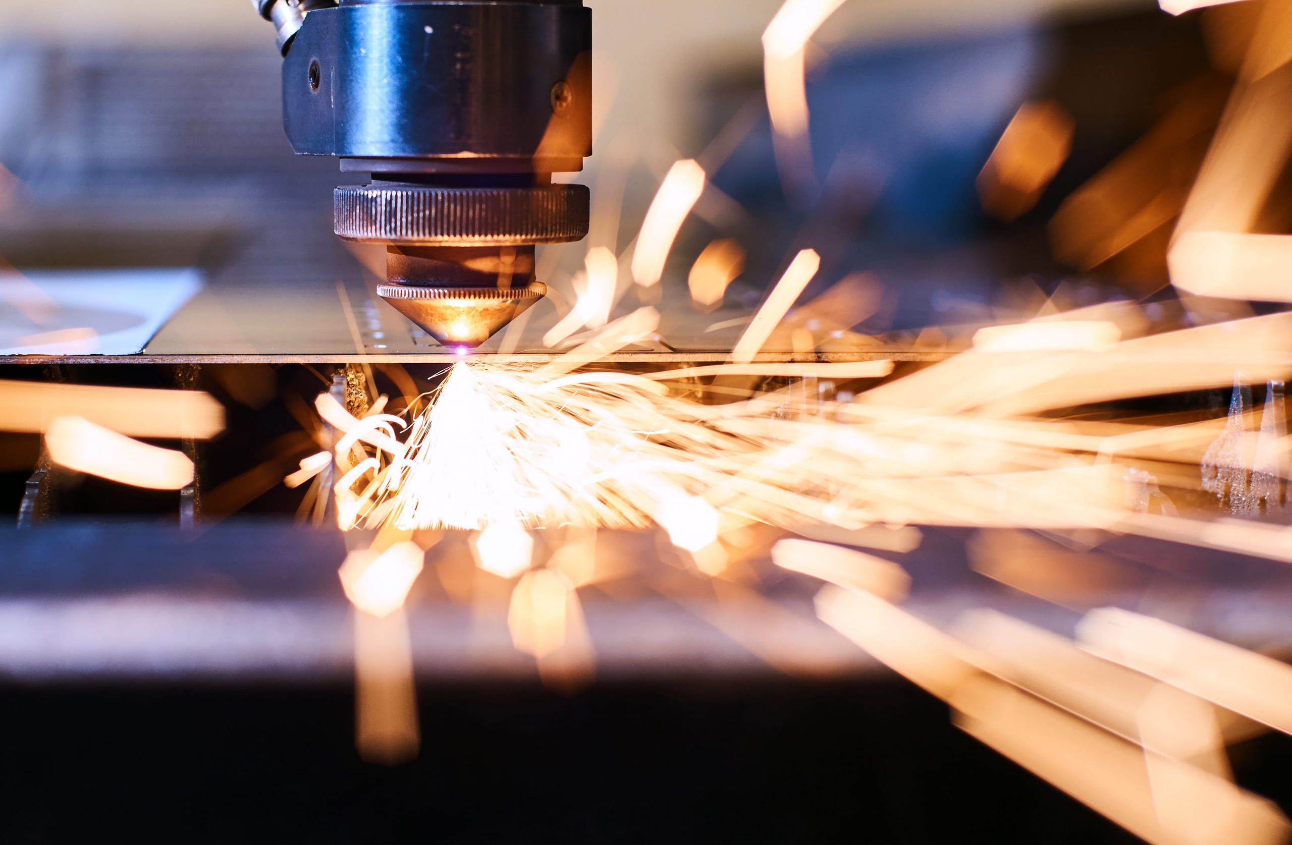 Close up of using a laser to cut metal with sparks flying