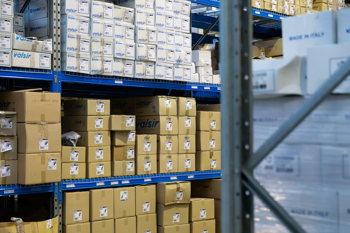Stacked boxes with stock on shelves in a warehouse