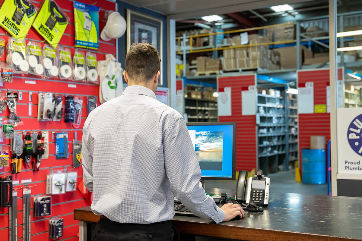 A shot from behind of a Galvins employee using their compyter at the sales counter with the warehouse in the background