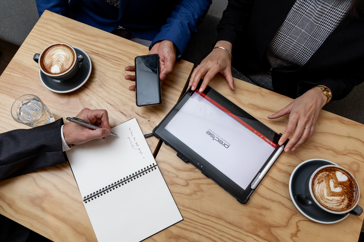 Precise workers meeting in a coffee shop with both technology and old school notetaking