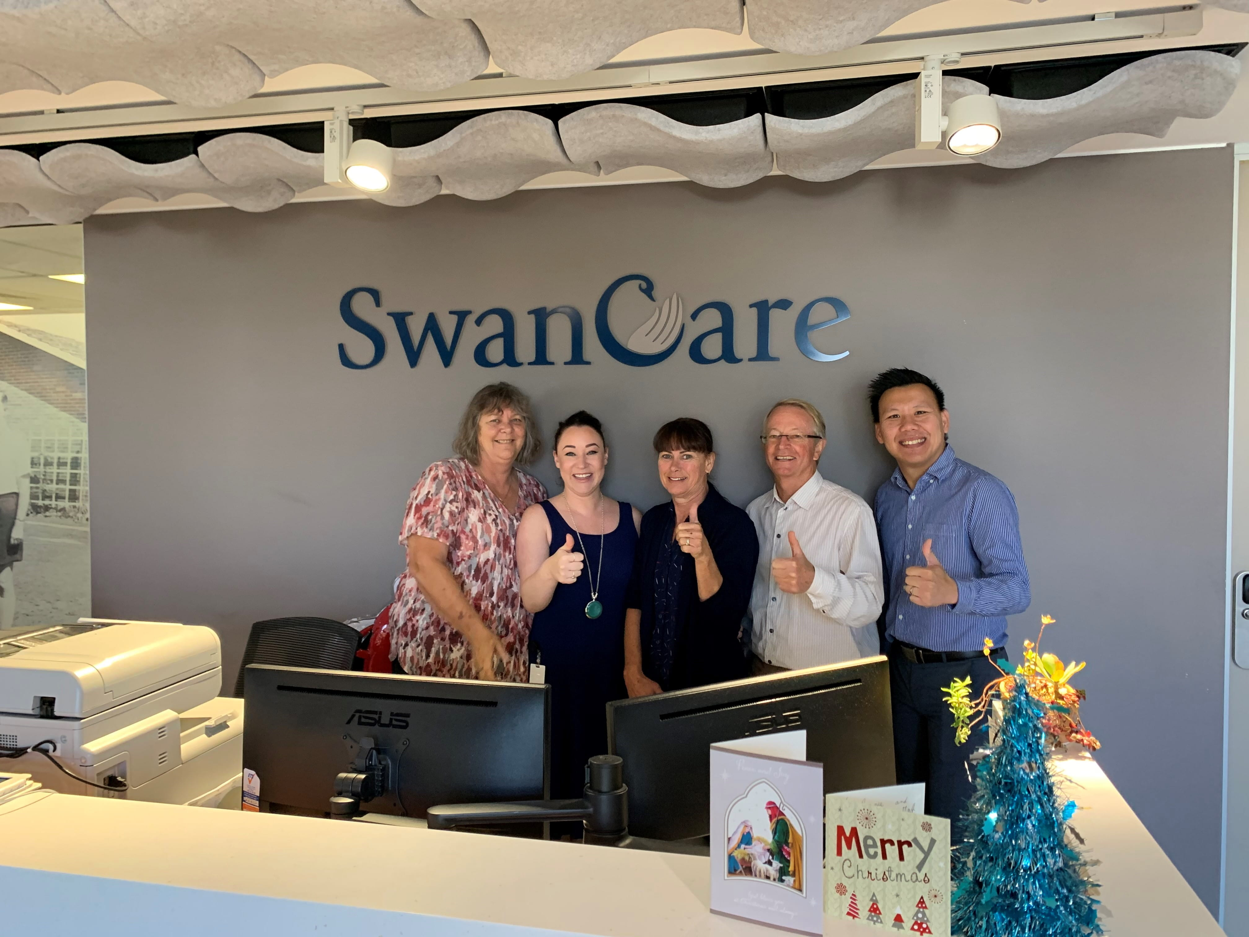Swan Care team giving the thumbs up beneath their sign