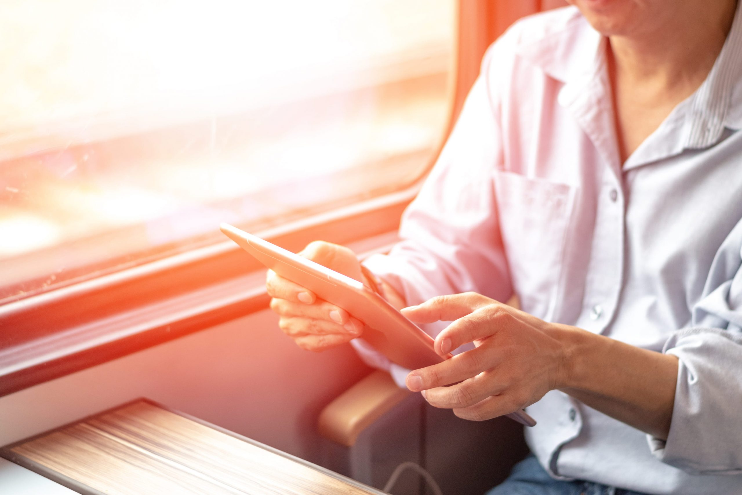 Person using a tablet to access reporting remotely on train commute into work