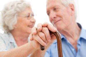 Older couple holding hands in aged care facility